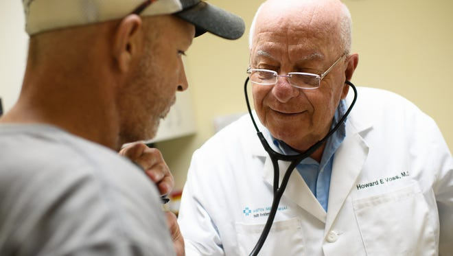 Dr. Howard Voss, right, listens to the heart of patient Chea Scott.