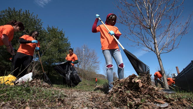 New Jersey Community Development Corp. holds a cleanup in the Great Falls District at William Carlos Williams Plaza as part of Global Youth Services Day on Saturday, April 21, 2018. Taeisha Kelley, of Paterson, rake leaves and debris.