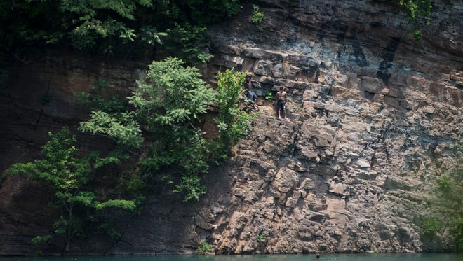 People prepare to jump off the cliffs just before a park supervisor warns them over a speaker not to at Fort Dickerson Quarry in South Knoxville Tuesday, June 5, 2018.