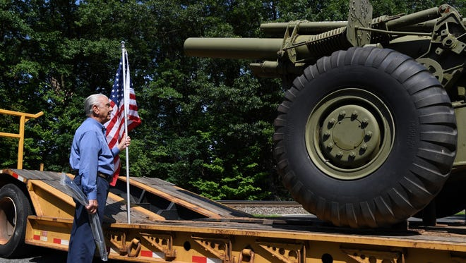 Domenick Iacovelli, a Korean War Air Force veteran, holds a flag as he waits to attach the flag to a flatbed that is moving a howitzer used in WWII from the property of the Woodcliff Lake VFW on Saturday, June 9, 2018. The howitzer is being moved to the Roseland VFW. Iacovelli lives in Sun City West, Arizona.
