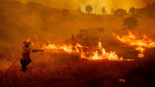 A firefighter scrambles to stop a wildfire as wind drives embers across Highway 20 near Clearlake Oaks, Calif., on July 1, 2018.