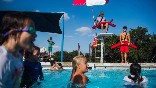 Leslie Botts, 70, in chair and below, prepares for a guard switch with Ian Samoson, 18, at the Balcones neighborhood pool in Austin, Texas. The city is having trouble hiring young lifeguards this summer, so it started recruiting older ones through ads in newspapers and utility bills.