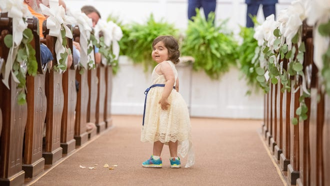 Skye Savren-McCormick of Ventura pauses during her duties as flower girl at Hayden Ryals wedding in Alabama. Ryals donated her bone marrow to Skye who was born with a rare form of leukemia.