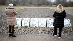 Visitors stand in front of pictures of prosecuted persons