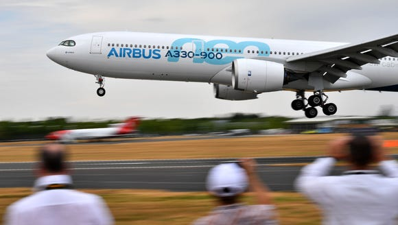 Visitors watch as an Airbus A330-900neo lands during
