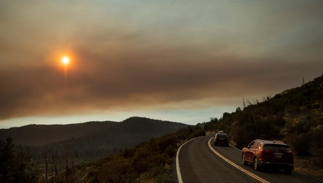 As smoke from the Ferguson Fire fills the sky, vehicles leave Yosemite Valley in Yosemite National Park, Calif., on Tuesday, July 24, 2018. Parts of the park, including Yosemite Valley, will close Wednesday as firefighters work to stop the blaze. (AP Photo/Noah Berger) ORG XMIT: CANB102
