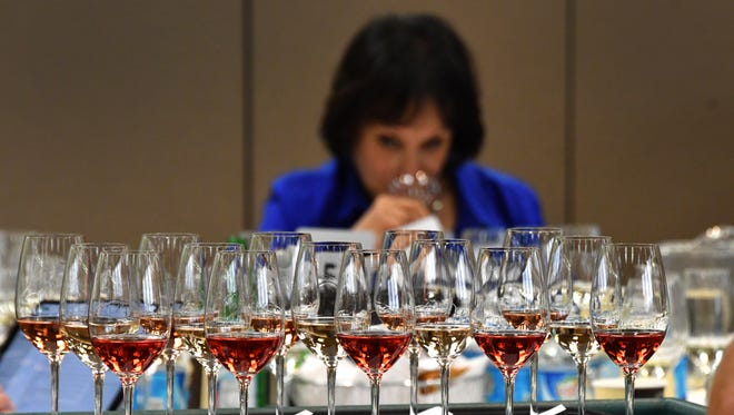 A flight of rosé wines awaits judges, such as Master Sommelier Madeline Triffon, who sorts through Michigan wines during the annual Michigan wine competition held at MSU's Kellogg Center in 2018.