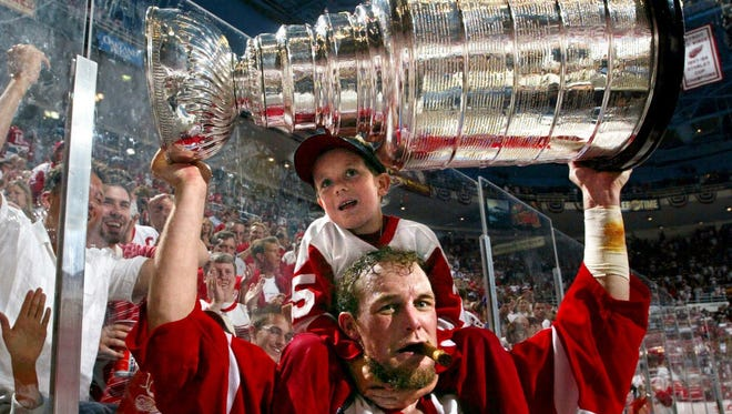 Darren McCarty with his 5 year old son on his shoulders raises the Stanley Cup during post game celebrations after their Game 5 win over the Carolina Hurricanes in June 2002.