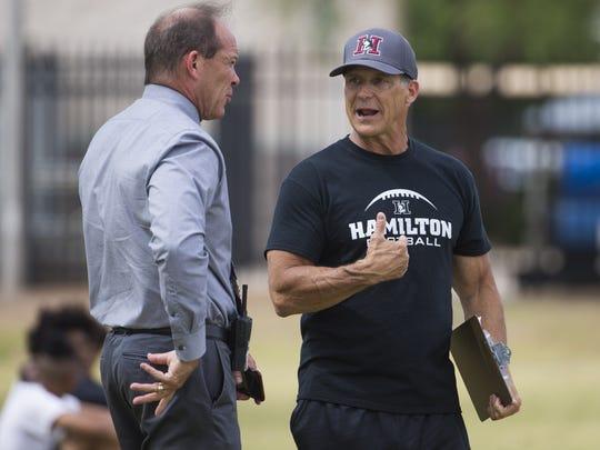 Hamilton High School Principal Ken James (left) talks with interim football coach Richard Baniszewski during spring practice in Chandler on April 24, 2017.