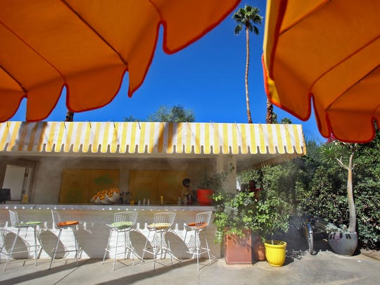 An outdoor lemonade stand serves poolside drinks and offers outdoor seating at the Parker Palm Springs.