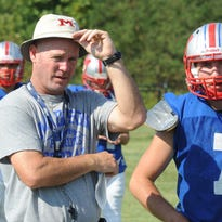 Madison High School football Coach Mark Gosnell watches alongside quarterback Tyler Rogers during practice at Madison High School.  Gosnell was charged Monday with misdemeanor stalking.