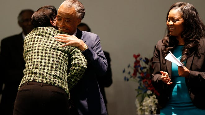 Melowese Richardson who was convicted of Voter Fraud and released early from a five year prison sentence is hugged by Rev. Al Sharton as he joins State Representative Alicia Reece to kick off the petition drive for Ohio Vote at Word of God Deliverance Family Life Center in Forest Park.