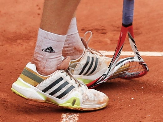 Ernests Gulbis of Latvia steps on his racket during his men's singles match against Roger Federer of Switzerland.