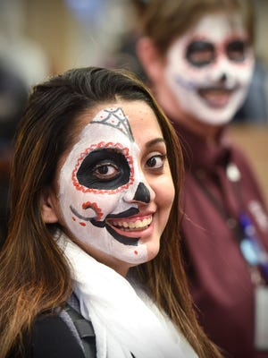 Sahreen Ijaz smiles after having her face painted during a Dia de los Muertos and Halloween Bash Tuesday, Oct. 31, at St. Cloud Technical & Community College in St. Cloud.