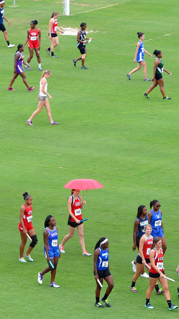 Athletes head are walked to their positions along the track before the start of the girls' 4x100 meter relay during the second day of the VHSL 2A state track and field championships in Radford on Saturday, June 7, 2014.