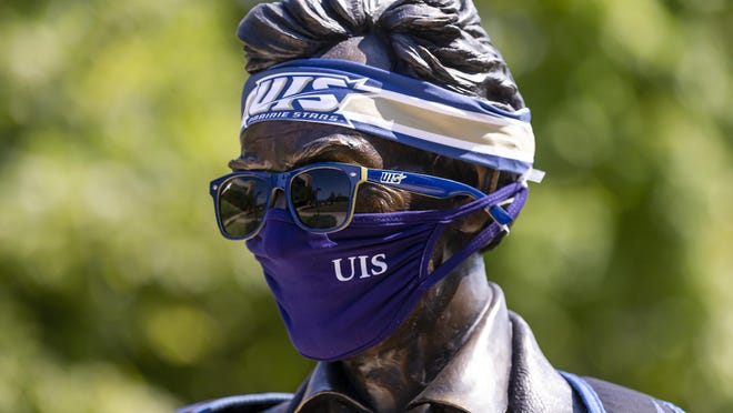 The statue of Abraham Lincoln outside University Hall is obeying the rules that all students, faculty and staff must wear face masks while on campus on the first day of classes at the University of Illinois Springfield, Monday, August 24, 2020, in Springfield, Ill.