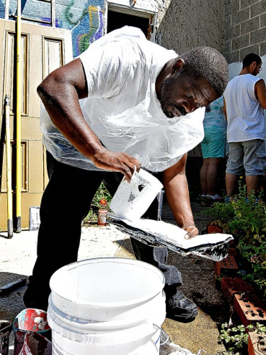 Kenneth Brown of York City refills a paint tray while priming the walls at the garden.