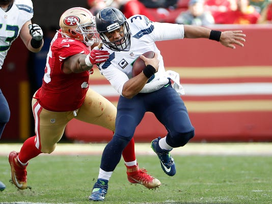 Seattle Seahawks quarterback Russell Wilson (3) scrambles from San Francisco 49ers linebacker Ahmad Brooks during the first half of an NFL football game in Santa Clara, Calif., Sunday, Jan. 1, 2017. (AP Photo/Tony Avelar)