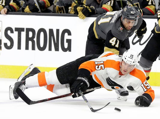 Vegas Golden Knights right wing Pierre-Edouard Bellemare (41) reaches under Philadelphia Flyers center Jori Lehtera (15) during the first period of an NHL hockey game Sunday, Feb. 11, 2018, in Las Vegas. (AP Photo/Isaac Brekken)