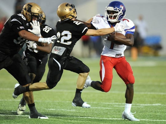 Abilene High defensive back Doak Holloway (22) tries to bring down Cooper running back Devin Johnson (7) during the first quarter of the Cougars' 55-38 loss to Abilene High in the crosstown football game on Friday, Sept. 9, 2016, at Shotwell Stadium.