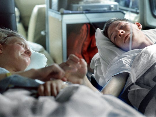 James Stolpa holds the hand of his wife, Jennifer, on Jan. 7, 1993, as the two ride in an ambulance from Northern California to Reno. The couple, with their infant child, had become snowbound for days in northern Washoe County before James hiked out through the snow for help. Jennifer and her baby waited in a primative snowcave with little winter clothing in a story that drew worldwide attention.