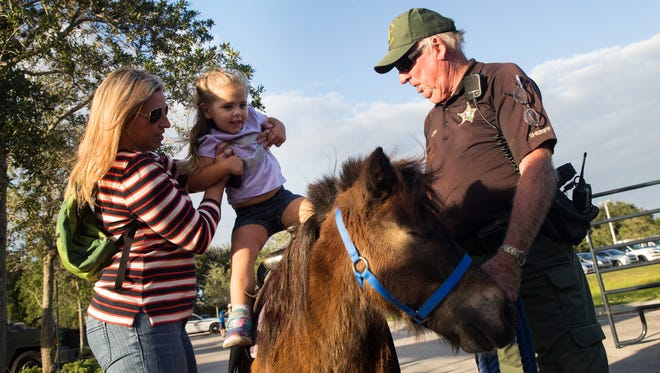 Maggie Harrison, 2, gets lifted onto the pony ride during the Celebrate Safe Communities event at the Vanderbilt Presbyterian Church on Monday, Oct. 10, 2016, in Naples. Other festivities included cookouts, bounce houses, wall climbing and refreshments. Celebrating Safe Communities is designed to heighten crime prevention and drug prevention awareness, generate support for and participation in local anti-crime efforts, and strengthen neighborhood spirit and police-community partnerships.