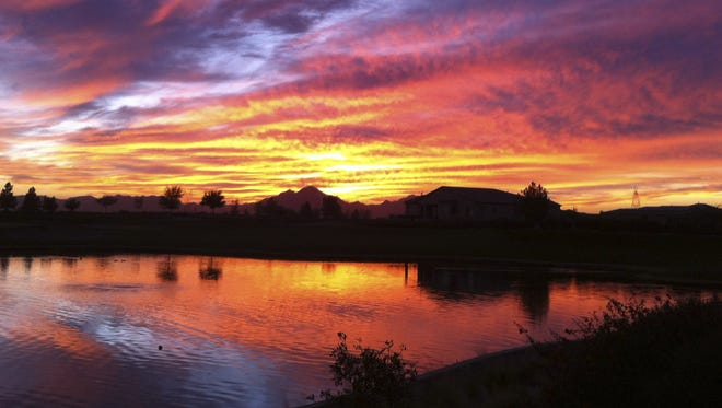 A breathtaking sunset reflecting in the lake at the Encanterra Country Club in the San Tan Valley area.