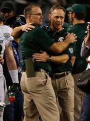 Michigan State head coach Mark Dantonio hugs defensive coordinator Pat Narduzzi following MSU's 42-41 victory over Baylor in the Cotton Bowl Classic. It was Narduzzi's final game with the Spartans, as he will take over as head coach at Pittsburgh.