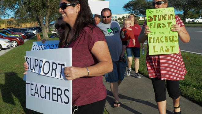 Teachers picket in front of School Board headquarters in Viera Tuesday evening. Teachers are protesting the School Board's latest offer of a 1% raise in pay.