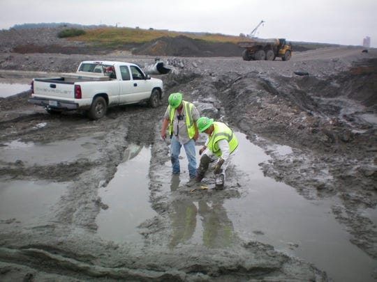 This photo depicts unprotected workers mired in wet coal ash sludge.
