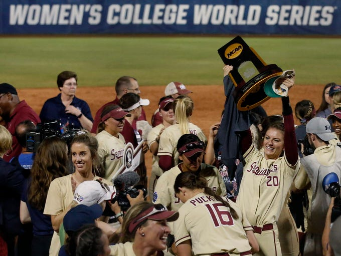 Florida State's Kylee Hanson holds the trophy as players