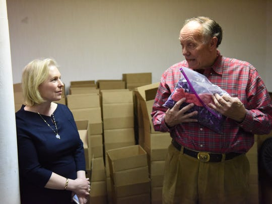 Brud Hodgkins, right, owner of Indoor Organic Gardens, shows Sen. Kirsten Gillibrand, left, the size difference between microgreens and more mature vegetables.