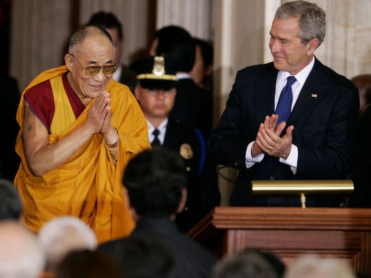 President George W. Bush (right) applauds as the Dalai Lama arrives for the Congressional Gold Medal ceremony in the Capitol Rotunda on Capitol Hill in Washington on Oct. 17, 2007.