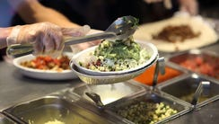 Chipotle restaurant workers fill orders for customers