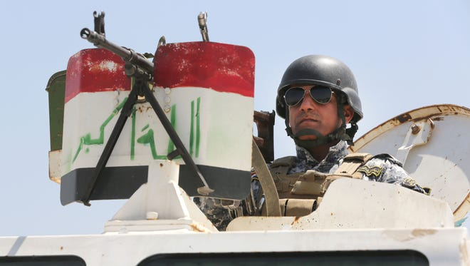 An Iraqi federal policeman standing on top an armored vehicle secures a checkpoint Sunday in Baghdad.