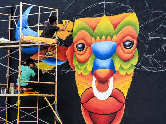 Local artists Snyder Macaraeg, 29, top, and Austin Domingo, 27, blend hues as they paint a mural of a multi-colored carabao on the side of a building in Hagåtña on Tuesday, Oct. 3, 2017. The project is one of several murals coordinated by Guam Art eXhibit and Pow!Wow! Guam.