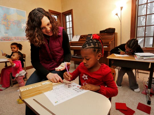 Carlee Dawodu works with her daughter Elizabeth, 4, on math Wednesday, December 17, 2014, in their Lafayette home. With a gap in he ages of all four of her daughters, Dawodu prefers homeschooling as a way to keep the children together.
