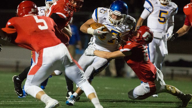 Sioux Falls O'Gorman Catholic High School's Sam Burnison (37) attempts to advance as Rapid City Central High School's Isaak Iverson (84) tackles him during Friday's game at O'Harra Stadium.