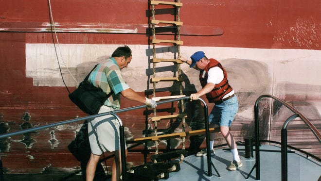 A Lakes Pilots Association pilot prepares to climb the ladder up the side of a moving vessel.