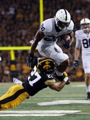 Penn State's Saquon Barkley tries to hurdle Iowa's Amani Hooker.