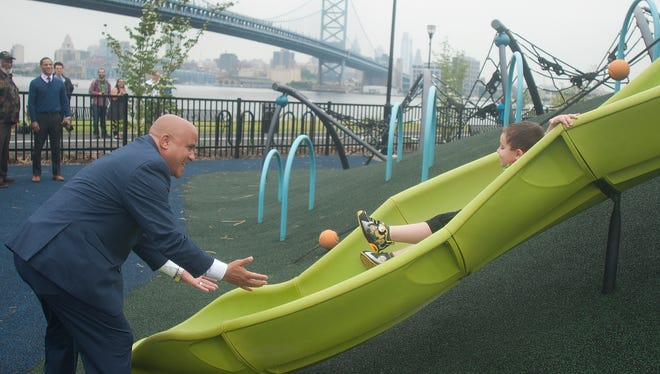 Xavier Reyes goes down the slide as Councilman Frank Moran waits for his landing during the official opening of Cooper's Poynt Waterfront Park, a 5-acre park on the site of what used to be Riverfront State Prison.