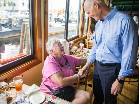 Gov. Rick Scott visited with Marilyn Christoph of Wilmington, N.C., who was dining at Pinchers while Scott toured the many businesses at Tin City, which officially reopened during a ribbon-cutting Monday, Oct. 9, 2017, after damage from Hurricane Irma halted business.