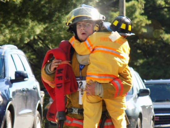 A firefighter runs in full gear while carrying a child