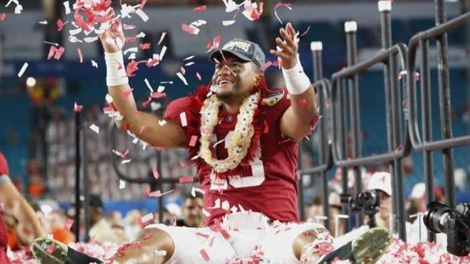 Alabama quarterback Tua Tagovailoa throws confetti in the air after winning the Orange Bowl.