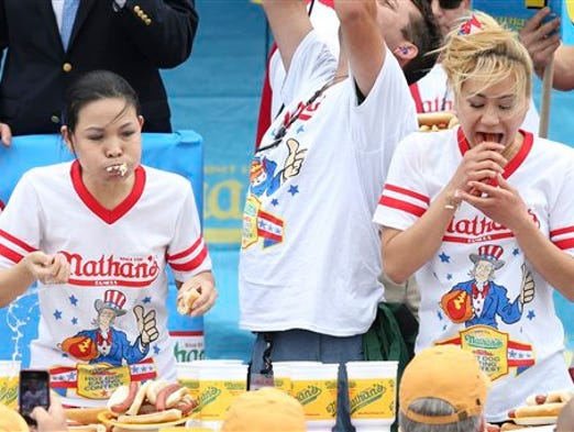 Sonya Thomas, left, and Miki Sudo, right, compete at the Nathan's Famous Fourth of July International Hot Dog Eating contest at Coney Island, Friday, July 4, 2014, in New York. Sudo defeated the reigning champion Thomas by eating 34 hot dogs and buns. (AP Photo/John Minchillo)