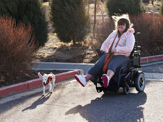 Amanda 'Mandy; Morgan takes her dog, Ziggy Marley, for a walk at Harmony Road Apartments on Monday. Residents are opposed to a plan for a neighboring apartment development to use their driveway, saying they are concerned for their safety.