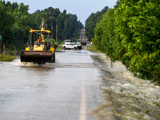 A worker drives a backhoe that was used to remove trees and clutter from the road in the morning hours after flash floods swept through low lands and creek beds at Highway 18 in Medon, Tenn., Monday, July 16, 2018.