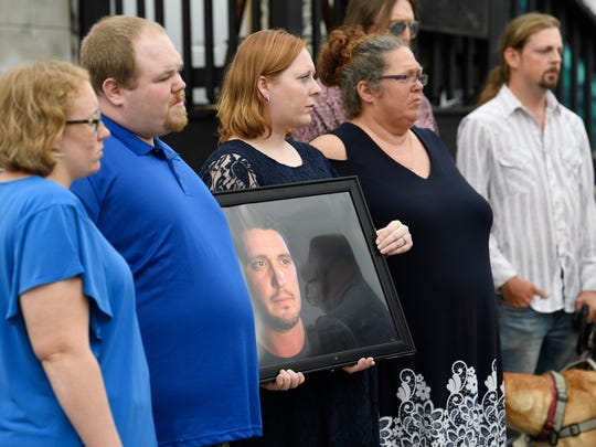 The family of Nashville shooting victim Bartley Brandon Teal  holds a press conference at The Cobra Tuesday, Aug. 21, 2018, in Nashville, Tenn. His sister, Amanda Tuttle, holds hisportrait.