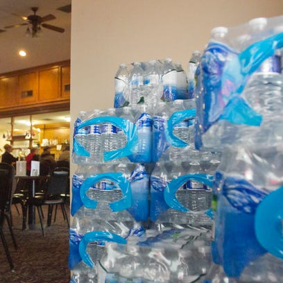 A stack of bottled water stands near the door of the