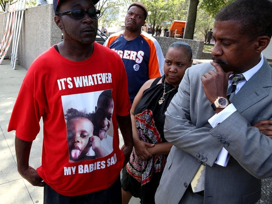 With his lawyer, Karri Mitchell, and wife, Yvette Johnson, looking on, Kevin Kellom shows off his T-shirt picturing his son Terrence Kellom and grandson Terrence Kellom Jr.